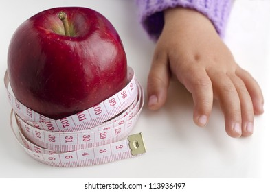 Measuring meter over a diet apple with child hand.