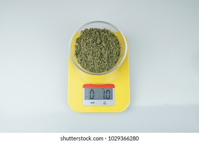 Measuring of one ounce of ground medical cannabis on glass plate on yellow measuring scale on white background, top view, close-up, selective focus