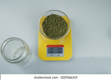Measuring of one ounce of ground medical cannabis on glass plate on yellow measuring scale on white background, with empty glass jar on side, top view, close-up, selective focus