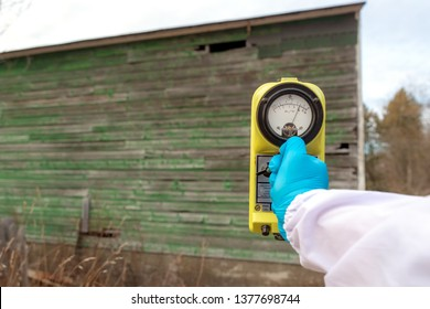 Measuring radiation at an old building. A blue gloved hand holds a radiation meter up to an old building, the needle shows a large amount of radiation. Dark overcast day.