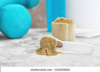 Measuring spoons with hemp protein powder on table