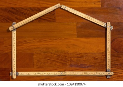 Measuring stick folded in the shape of a house on a wooden background