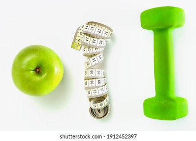 measuring tape apple and dumbbell on a white background. workout slimming and healthy nutrition concept. copy space.