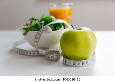 Measuring tape around the apple, bowl of green salad and glass of juice. Weight loss and right nutrition concept
