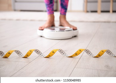 Measuring tape and blurred woman on scales