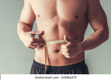 Measuring tape. Cropped image of attractive young sports man which measures his waist on gray background.