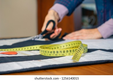 Measuring tape with dressmaker cutting fabric with scissors in the background. Selective focus on measuring tape on foreground
