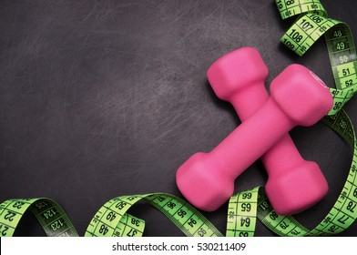 measuring tape and dumbbells on a black background
