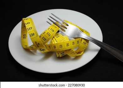 Measuring tape and fork on black background. Diet concept.