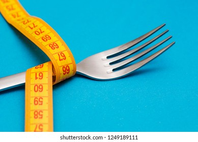 Measuring tape with fork on blue background. Concept of weight loss. Weight management. Healthy lifestyle. Weight loss health issue. Diet concept