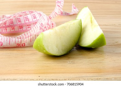 Measuring tape and green apple on wooden background.