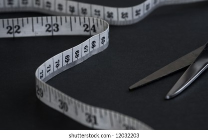 Measuring tape isolated on a black background with scissor