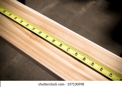 A measuring tape laid out along a length of wood.