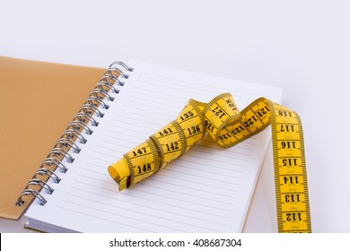 Measuring tape near a notebook on a white background