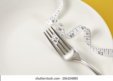 Measuring tape on a fork - dieting concept image