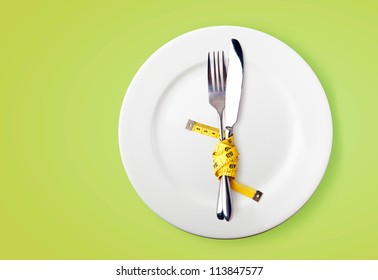 Measuring tape on a fork and knife  - dieting concept image