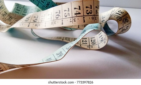 Measuring tape on white paper background. Selective focus.