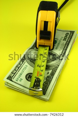 A Measuring Tape Over Bills Of One Hundred Dollars