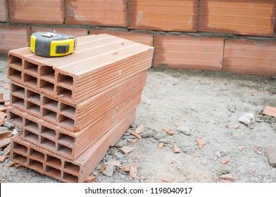 Measuring tape over clay-based bricks. Closeup
