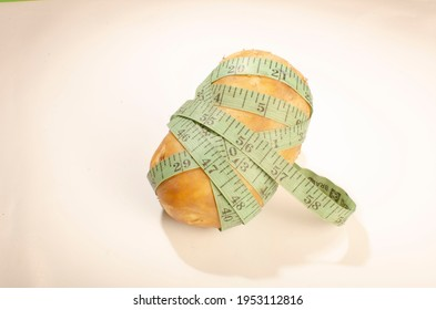 A measuring tape is put around a potato to signify the effects of overweight and the importance of weight loss.