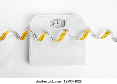 Measuring tape and scales on white background, top view. Concept of weight loss