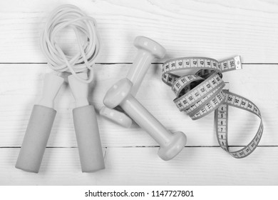 Measuring tape and sports equipment. Healthy lifestyle and losing weight concept. Barbells, centimeter and jump rope top view on white background. Gym tools in cyan blue on wooden backdrop.
