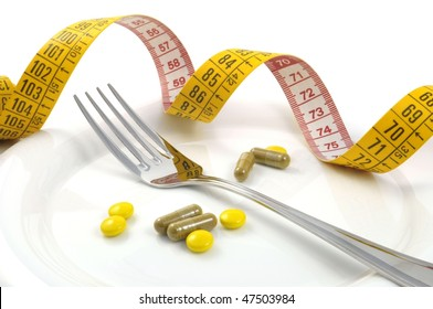 measuring tape with tablets and fork - diet concept