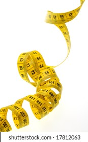 A measuring tape is very yellow as a spiral up and lays down on white background.