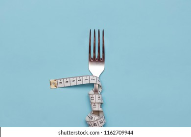 Measuring tape wrapped around a fork lying on a blue background. Proper nutrition. Medical starvation. Diet for weight loss concept. Free space for text.