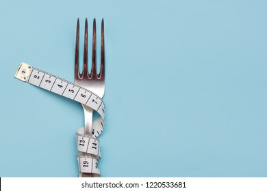Measuring tape wrapped around a fork lying on a blue background. Proper nutrition. Medical starvation. Diet for weight loss concept. Free space for text or advertisement.