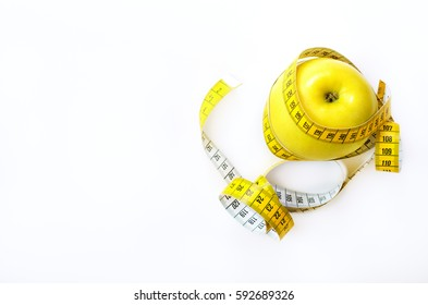 Measuring tape wrapped around fresh tasty yellow apple isolated on white background. Diet, weight loss, fitness, sport concept. Spring and summer fruit. Copy space