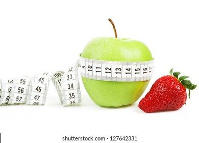 Measuring tape wrapped around a green apple and strawberry as a symbol of diet concept