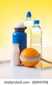 Measuring tape wrapped around an orange, bottled water and blue sport bottle as a symbol of diet on yellow background.