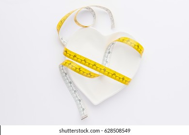 measuring tape wrapped around plate isolated on white, healthy living concept
