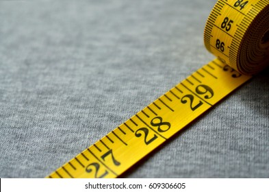 The measuring tape of yellow color with numerical indicators in the form of centimeters or inches lies on a gray knitted fabric. Background image about sewing sportswear for people, who slimming