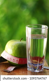 measuring tape,green apple on table