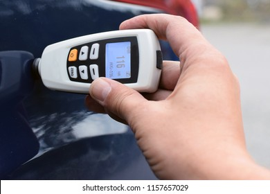 Measuring thickness of the car paint coating with paint thickness gauge.