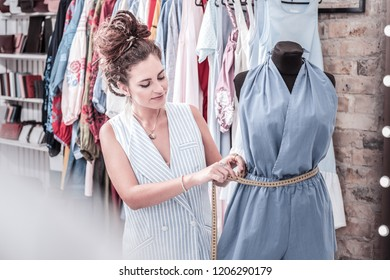 Measuring waistline. Fashion designer feeling busy while measuring waistline of jumpsuit from new collection