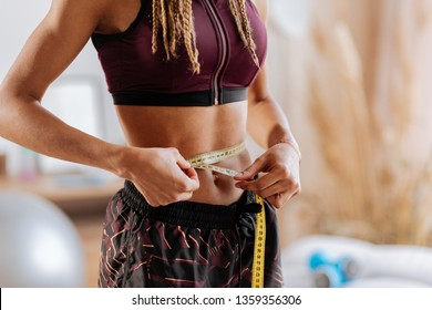 Measuring waistline. Slim woman with nice abs wearing sport shorts and top measuring her waistline