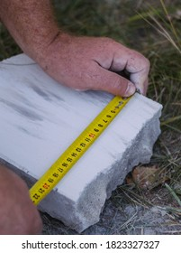 measuring the width of a white brick with a yellow tape measure on the ground