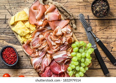 Meat antipasto board, pancetta, salami, sliced ham, sausage, prosciutto, bacon with grape and parmesan cheese. Wooden background. Top view