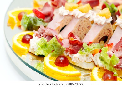 Meat assortment with salad, oranges and grapes, focus on food in the bottom third
