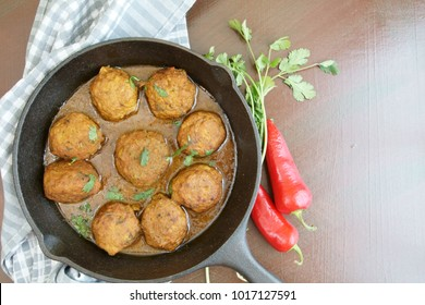 Meat balls or meat kofta curry in masala gravy on a wooden background with copy space.