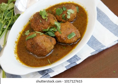Meat balls or meat kofta curry in masala gravy on a wooden background.