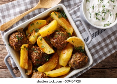 Meat balls with potatoes in a baking dish and sour cream close-up on a table. horizontal view from above