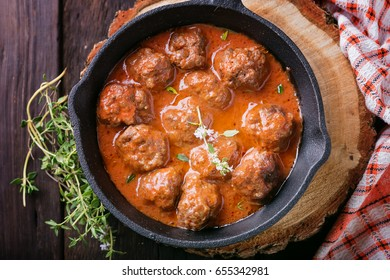 Meat balls in tomato sauce in a cast iron skillet, close up