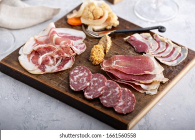 Meat charcuterie board with pickled vegetables and mustard