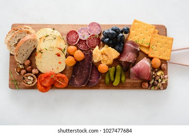 Meat and cheese plate.Traditional italian antipasto, cutting board with salami, cold smoked meat, prosciutto, ham, cheeses, olives, capers on white background. Cheese and meat appetizer. Top view.