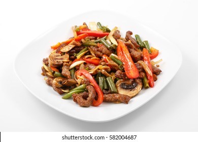 meat in Chinese, pork, Chinese sauce, mushrooms, green beans, bell pepper in a white plate on a white background