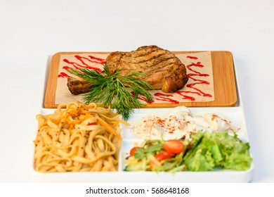 Meat chops with grilled ribs with pasta and vegetables